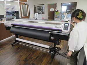 Two female designers operate the printer.